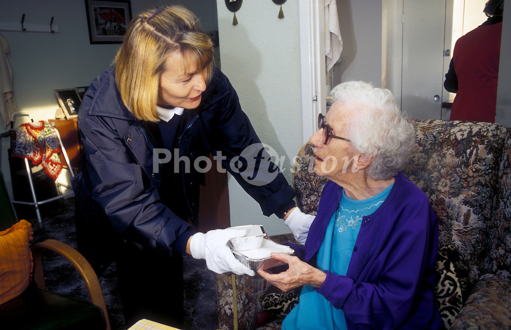 Meals on wheels worker handing over delivery to client