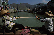 Hong Kong. Sampan crossing the river  in Cheng Chau island       /  embarcadère  des Sampans à Cheng Chau  /  Les derniers jours du village de Tai O- Tai 0 village sur l'île Lantau à  HongKong charmant petit village de pêcheurs sur pilotis dont la seule attraction est la petite barque tiree par deux vielles dames, qui permet de relier la presqu'île à Lantau. l'île sera transfiguree par la construction du nouvel aeroport  ile de Cheng Chau       /  R94/29    L0007507  /  R00094  /  P0001939