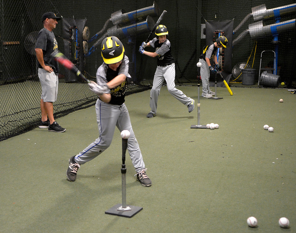 gbs073117o/SPORTS -- Eastdale Little Leaguer Christian Armijo, 13, front, hits balls during an indoor practice because of rain at the Back 2Back batting cages on Monday, July 31, 2017. (Greg Sorber/Albuquerque Journal)