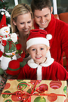 Boy (5-6) holding present in front of parents