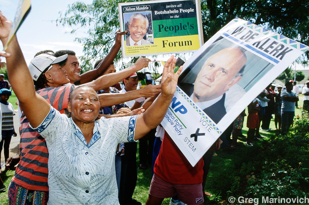 Coloured South Africans welcome President FW de Klerk to a National party rally as ANC supporters hold up a poster of Nelson mandela, 1994, South Africa.