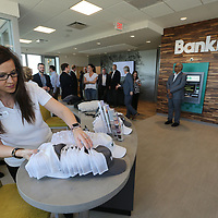 Jamie Lynn Franks makes sure all the sovenir hats are in place as Bank Plus opens it's newest location on North Gloster Street in Tupelo Friday.