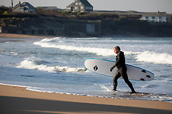 © Licensed to London News Pictures. 27/03/2020. Wadebridge, UK. A surfer on Constantine Bay beach, Cornwall, this morning. British Prime Minister Boris Johnson has ordered a lockdown to slow the spread of Coronavirus (COVID-19) across the country. Photo credit : Tom Nicholson/LNP