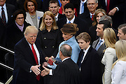 President Donald Trump shakes hands with Chief Justice John Roberts after being administered the oath of office as the 45th President surrounded by his wife Melania and five children January 20, 2017 in Washington, DC.