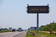 LED signs warning of extreme drought conditions in Texas on interstate 10 asking people to conserve water . The Drought in Texas will have long term environmental and finical impact.