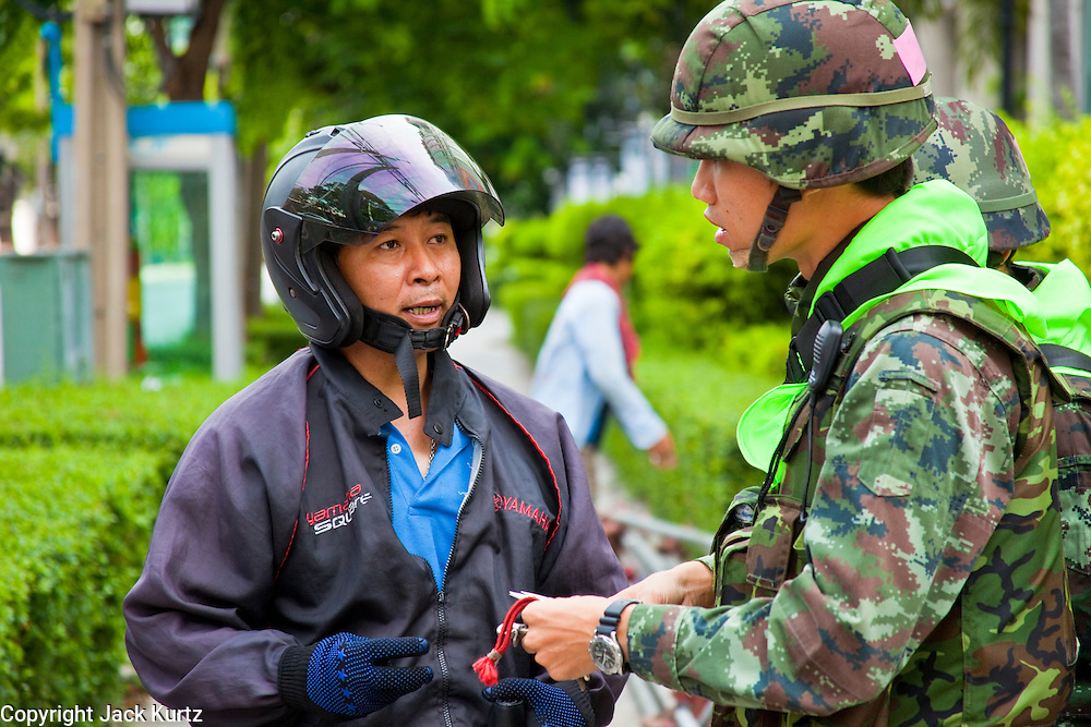 20 MAY 2010 - BANGKOK, THAILAND: A Thai soldier questions a man near the Ratchaprasong Intersection in Bangkok Thursday. The day after a military crackdown killed at least six people, Thai authorities continued mopping up operations around the site of the Red Shirt rally stage and battle fires set by Red Shirt supporters in the luxury malls around the intersection. PHOTO BY JACK KURTZ