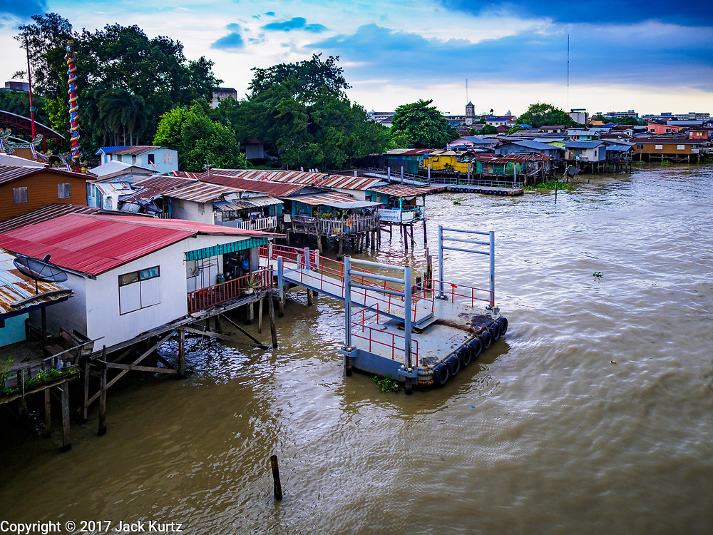 """20 JUNE 2017 - BANGKOK, THAILAND:   Riverfront homes in a community along the Chao Phraya River south of Krung Thon Bridge. This is one of the first parts of the riverbank that is scheduled to be redeveloped. The communities along the river don't know what's going to happen when the redevelopment starts. The Chao Phraya promenade is development project of parks, walkways and recreational areas on the Chao Phraya River between Pin Klao and Phra Nang Klao Bridges. The 14 kilometer long promenade will cost approximately 14 billion Baht (407 million US Dollars). The project involves the forced eviction of more than 200 communities of people who live along the river, a dozen riverfront  temples, several schools, and privately-owned piers on both sides of the Chao Phraya River. Construction is scheduled on the project is scheduled to start in early 2016. There has been very little public input on the planned redevelopment. The Thai government is also cracking down on homes built over the river, such homes are said to be in violation of the """"Navigation in Thai Waters Act."""" Owners face fines and the possibility that their homes will be torn down.              PHOTO BY JACK KURTZ"""