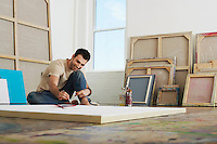 Artist painting on canvas lying on studio floor