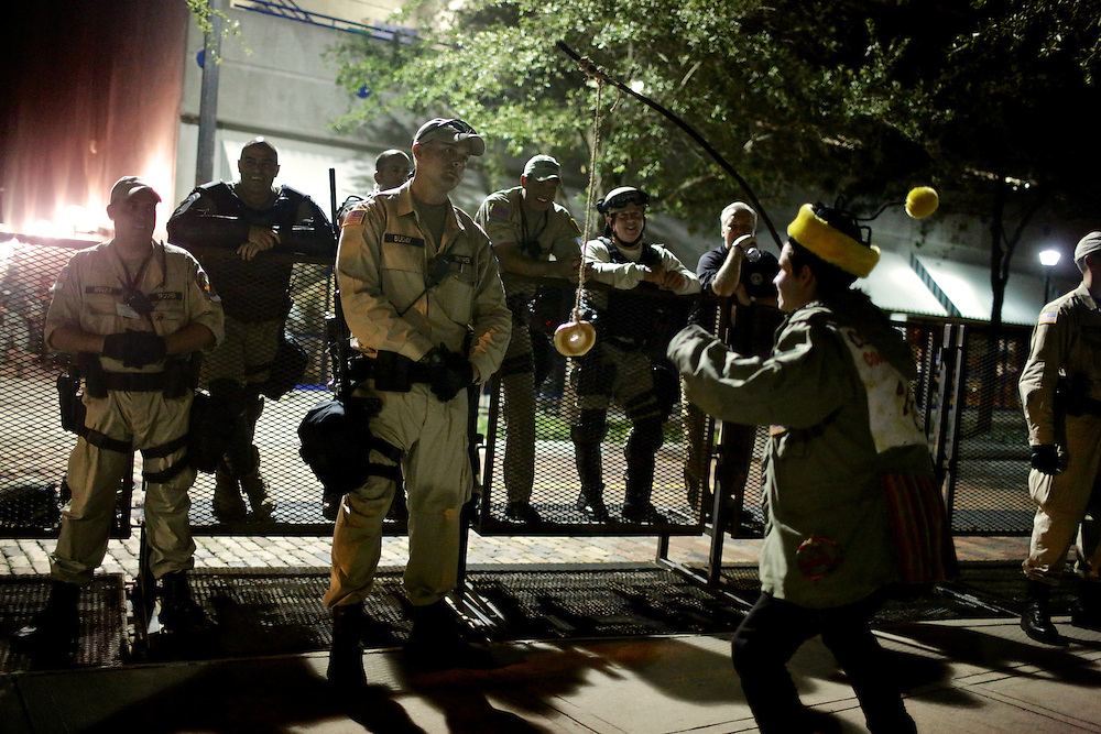 A protestor dressed like a clown dangles a bagel in front of law enforcement  at Lykes Gaslight Square Park in an unscheduled silent march during the 2012 Republican National Convention in Tampa, Fla. on Aug. 29, 2012.