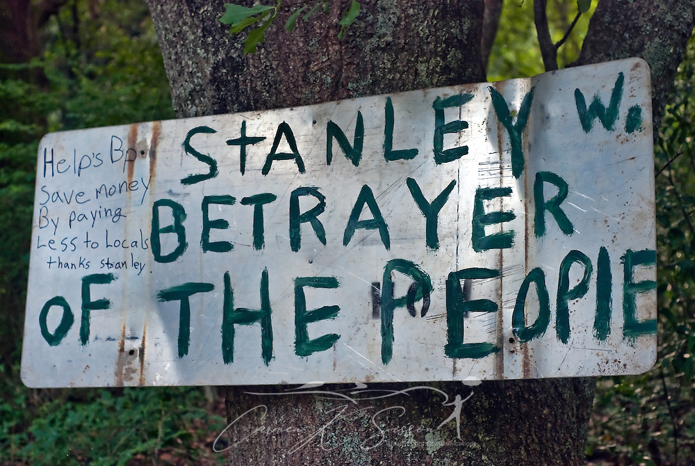 """A hand-painted sign on Padgett Switch Road, near the Bayou La Batre city limits, calls mayor Stan Wright a """"betrayer"""" for his decision to partner with BP in the operation of the Vessels of Opportunity Program. More than 500 people gathered at the city docks July 2, 2010 to protest the move, saying they fear the mayor's involvement will result in favoritism and pay cuts. Under the VOO program, local boaters and fisherman have been hired by BP to protect vulnerable areas from the Deepwater Horizon oil spill. (Photo by Carmen K. Sisson/Cloudybright)"""