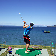 A golfer hits the ball towards a platform moored on the water at Lake Taupo. Taupo, New Zealand,, 8th January 2011. Photo Tim Clayton.