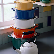 stack of Le Creuset pans in different colors by a window