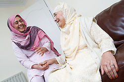 Older woman sharing a joke with younger woman,