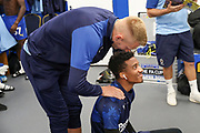 AFC Wimbledon striker Joe Pigott (39) rubbing AFC Wimbledon goalkeeper Nathan Trott (1) shoulders whilst in dressing room during the EFL Sky Bet League 1 match between AFC Wimbledon and Bristol Rovers at the Cherry Red Records Stadium, Kingston, England on 21 September 2019.