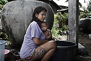 "KHAO LAK,SOUTHERN THAILAND,AUGUST 2012: A young Moken mother bathes her child in the Ban Tung Wa Moken village in Khao Lak, southern Thailand. The village is home to some 70 Moken families.<br /> The Moken are a nomadic sea people who live in and around southern Thailand, traditionally feeding of the fruits of the sea for eight months a year. But the 2004 Indian Ocean tsunami destroyed many livelihoods, and the Moken were forced onto the land.<br /> Brought to the world's attention by the natural disaster, the seafaring tribe is struggling to reconcile tradition and modernity, leaving behind their ""sea gypsy"" life for a modern existence"