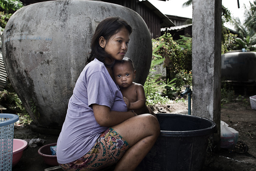 KHAO LAK,SOUTHERN THAILAND,AUGUST 2012: A young Moken mother bathes her child in the Ban Tung Wa Moken village in Khao Lak, southern Thailand. The village is home to some 70 Moken families.<br /> The Moken are a nomadic sea people who live in and around southern Thailand, traditionally feeding of the fruits of the sea for eight months a year. But the 2004 Indian Ocean tsunami destroyed many livelihoods, and the Moken were forced onto the land.<br /> Brought to the world's attention by the natural disaster, the seafaring tribe is struggling to reconcile tradition and modernity, leaving behind their &quot;sea gypsy&quot; life for a modern existence