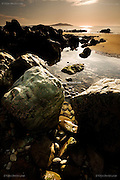 Revealed at low tide, a face in the boulders at Church Bay, North Anglesey. Holyhead Mountain in the background