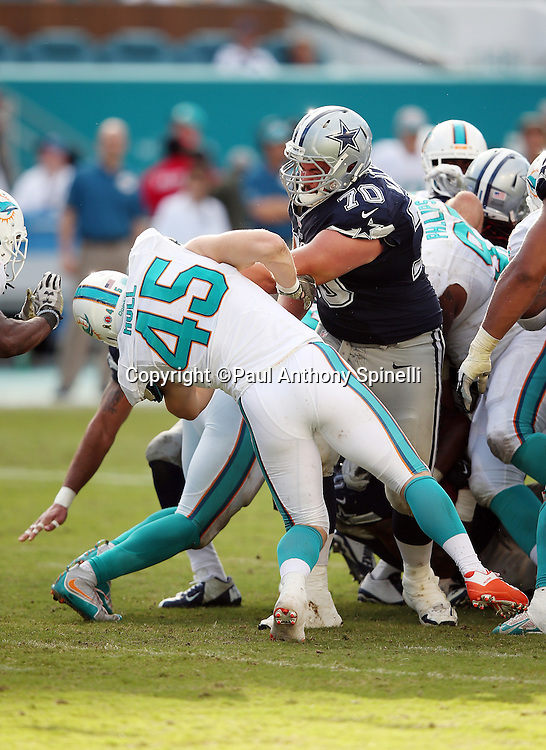 Miami Dolphins linebacker Mike Hull (45) gets knocked to the ground on a pancake block by Dallas Cowboys guard Zack Martin (70) during the 2015 week 11 regular season NFL football game against the Dallas Cowboys on Sunday, Nov. 22, 2015 in Miami Gardens, Fla. The Cowboys won the game 24-14. (©Paul Anthony Spinelli)