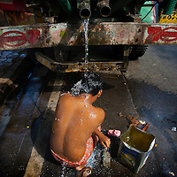 A man in Mumbai takes a bath in what ever water he can find.