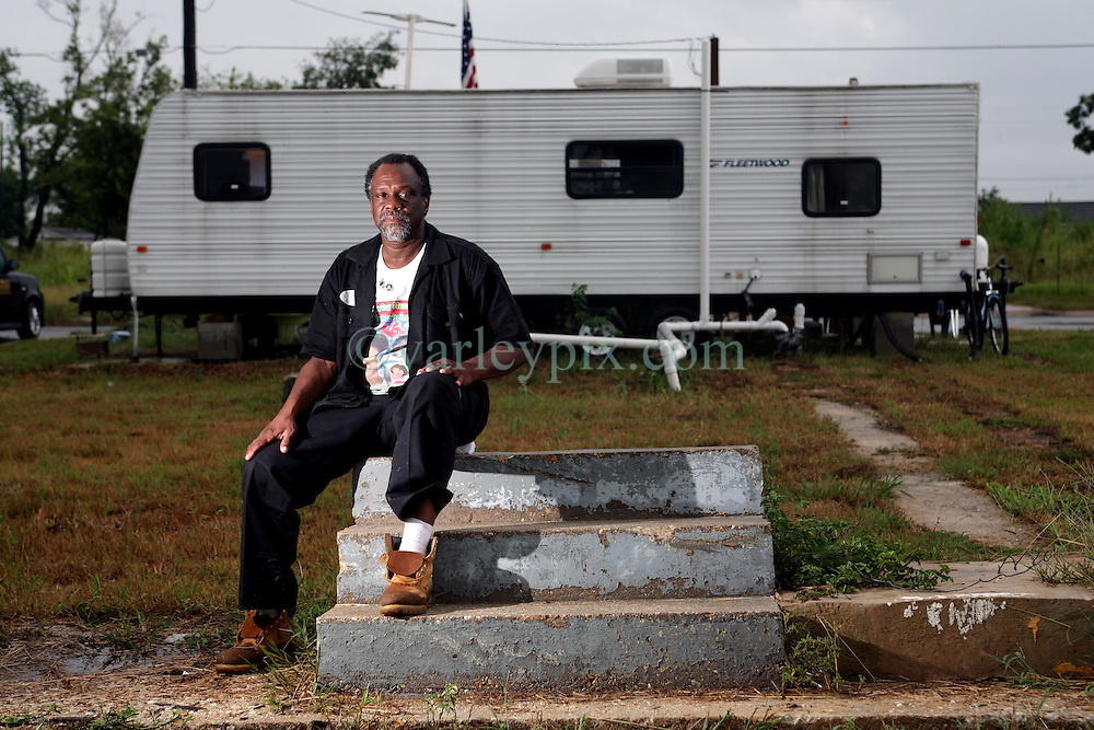 29 August 2007. Lower 9th Ward, New Orleans, Louisiana. <br /> Second anniversary of Hurricane Katrina. Robert Lynn Green Sr  sits on the steps of 1826 Tennessee Street in front of his trailer in the Lower 9th Ward. The steps are all that remain of his house after it was deluged by the levee breach just blocks from the steps. Robert lost his mother and grand daughter at the house when they perished in the terrible flooding. He lost hold of his grand daughter in the swirling floods. She was drowned. His mother was not found for 4 months when her skeleton was discovered in what remained of his washed away house. Robert hopes to rebuild. Many residents are struggling to return to the still derelict and decimated Lower 9th Ward.<br /> Photo credit©; Charlie Varley/varleypix.com