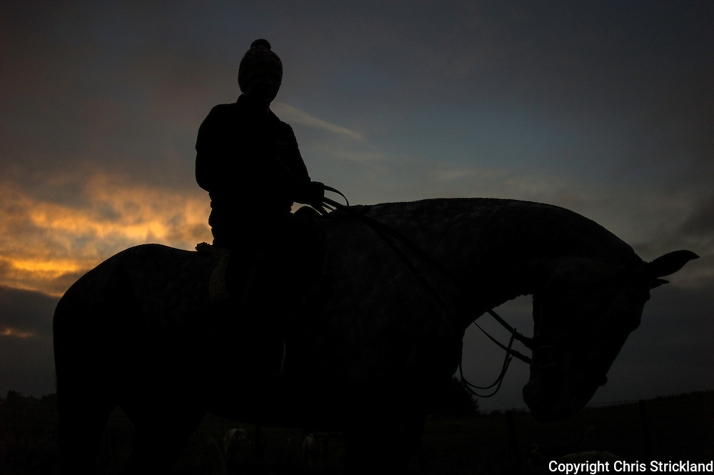 Georgina Shiels and horse George are silhouetted against a winter sky at the end of a days hunting.