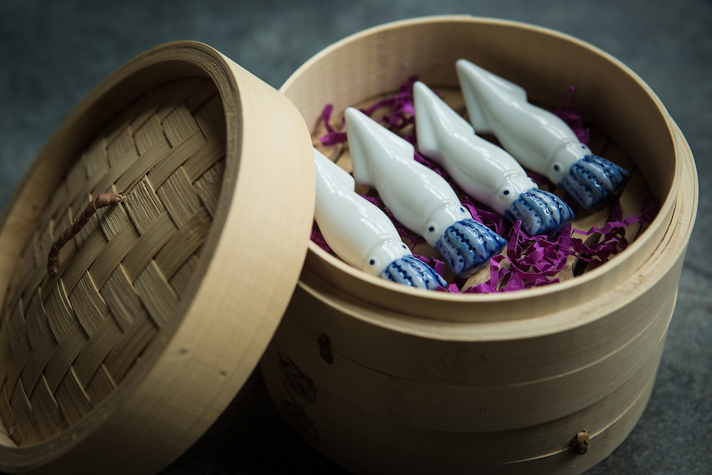 A bamboo steamer filled with porcelain squids.