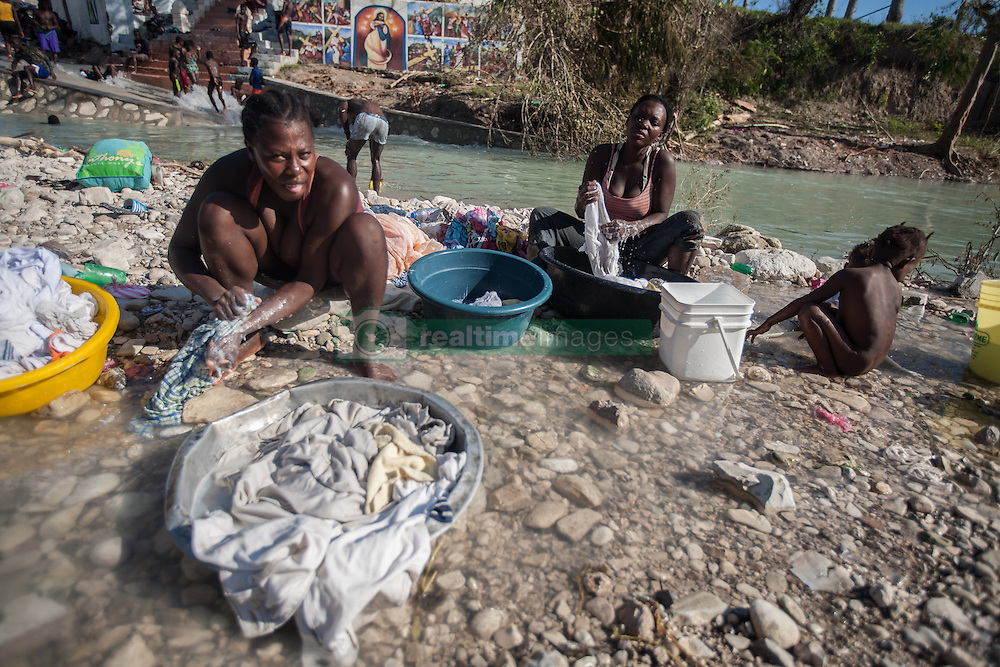 October 7, 2016 - Port Salute, Haiti - Women do laundry in the river in the town of Port Salute in South west while their children play around after hurricane Matthew caused their houses to collapse, on October 7, 2016. Bridges are washed away so aid has not been able to get to this area yet. Hurricane Matthew killed almost 900 people and displaced tens of thousands in Haiti before plowing northward on Saturday just off the southeast U.S. coast, where it caused major flooding and widespread power outages. (Credit Image: © Bahare Khodabande/NurPhoto via ZUMA Press)