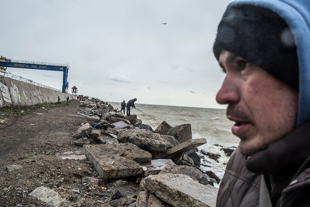 Aleksei, originally from Donetsk, braves a biting cold wind to fish off the wharf next to the city port on Sunday, March 20, 2016 in Mariupol, Ukraine.