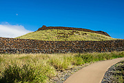The Moon rises over Pu'ukohola Heiau National Historic Site, which preserves an important Hawaiian temple on the Big Island of Hawaii, USA. Built to fulfill a historic prophecy, Puukohola Heiau is one of the last sacred structures built in the Hawaiian Islands before Christian influence. Kamehameha the Great (born in North Kohala) was advised by his kahuna (priest) to build Puukohola Heiau and dedicate it to the war god Kukailimoku (Ku) to help in his efforts to unite the Hawaiian Islands. The fortress-like heiau (sacred temple of the Hawaiian religion) was built overlooking the Kohala coast between 1790 and 1791. With help from European trade ships, warships, cannon, and military experience, King Kamehameha ultimately united the warring Hawaiian Islands in 1810. At the same time that George Washington was serving as the United States' first president, Kamehameha was using Puukohola Heiau to secure his mana or spiritual power to help unify the Hawaiian people. The massive structure (224 by 100 feet surrounded by walls 16-20 feet high) was built without mortar, using water-worn lava rocks believed to have been passed hand-by-hand in a human chain all the way from Pololu Valley, some 25 miles away. These lonely rocks on a dry desert hill mark an important era in Hawaiian history, just 28 miles north of Kona International Airport.