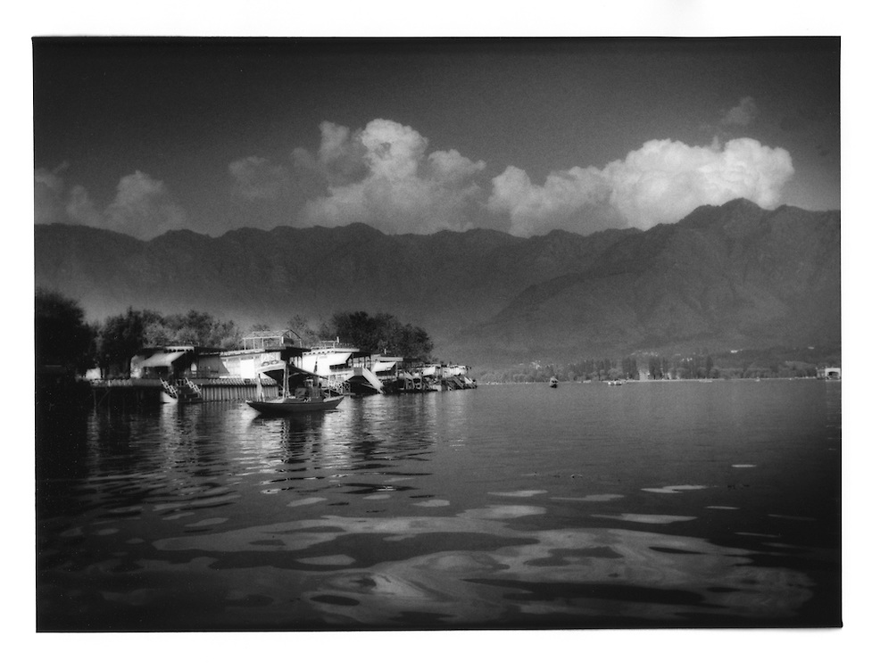 Perfect tranquility: Houseboats lining island shore within Dal Lake, Srinagar, Indian Administered Kashmir.   Tourism is Kashmir's primary source of income.  Tourist industry numbers, particularly the number of foreign tourists,  have been a mere fraction of what they had been before the current trouble beginning in the 1990's.
