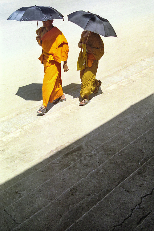In Luang Prabang, two monks protect themselves from the scorching noon sun with umbrellas, Laos, 2003.