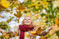 Portrait of beautiful woman playing with maple leaves in park