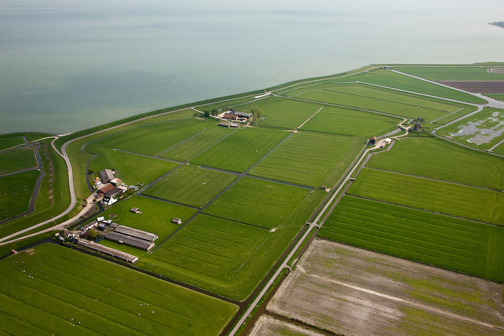 Nederland, Noord-Holland, Gemeente Zeevang, 28-04-2010; Polder de Etersheimerbraak. De polder is een voormalige 'braak' (dijkdoorbraak) die in 1632 bedijkt is (en vervolgens drooggemaakt). Tijdens de watersnood van 1916 stond het water aan de kruin van de Zeevangszeedijk (Zuiderzee- of IJsselmeerdijk). Om de dijk op te hogen - met klei, zijn in 1917 in de Etersheimerbraakpolder kleiputten gegraven (het gedeelte links van de diagonale weg)..The Polder Etersheimerbraak. The polder is a former 'breach' (levee failure) that was diked in 1632 (and subsequently dried). During the flood of 1916, the water stood at the top of the Zeevang seawall. To raise the top of the seawall, clay was needed and in 1917 clay pits were dug in the Etersheimerbraakpolder (the part left of the diagonal road)..luchtfoto (toeslag), aerial photo (additional fee required).foto/photo Siebe Swart
