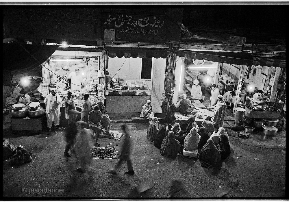 Peshawar: Women sit on the floor waiting for handouts of bread in a market area of Peshawar. Most are widows and rely on charities or beg nightly for food to feed their children.