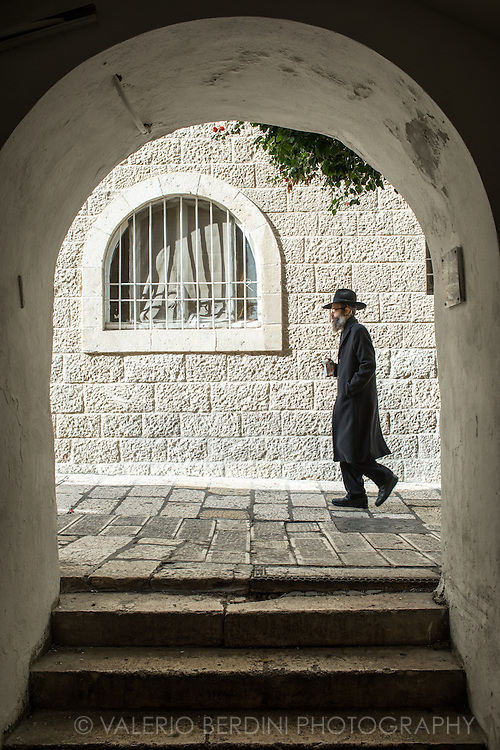 An Haredi Jew walks in Jerusalem Jewish Quarter in the Old City. The Jewish Quarter is one of the four traditional quarters of the Old City ofJerusalem and the only recently rebuilt after a history of destruction.<br /> While most residents of Jerusalem in the centuries preferred to live near members of their own community, there were Muslims living in the Jewish Quarter and Jews living in the Muslim Quarter. Many Jews moved to the Muslim Quarter toward the end of the 19th century due to intense overcrowding in the Jewish Quarter.<br /> In 1948 during the Arab-Israeli War, its population of about 2,000 Jews was besieged, and forced to leave en masse. A Jordanian commander is reported to have told: &quot;For the first time in 1,000 years not a single Jew remains in the Jewish Quarter. Not a single building remains intact. This makes the Jews' return here impossible.&quot;<br /> The Jewish Quarter remained under Jordanian occupation until the Six-Day War in June 1967 when Israel occupied it. During the first week after taking the Old City, the Moroccan Quarter was razed to create a plaza at the foot of the Western Wall.<br /> In April 1968, the government expropriated 129 dunams (about 32 acres) of land which had made up the Quarter before 1948. In 1969, the Jewish Quarter Development Company was established under the auspices of the Construction and Housing Ministry to rebuild the desolate Jewish Quarter.
