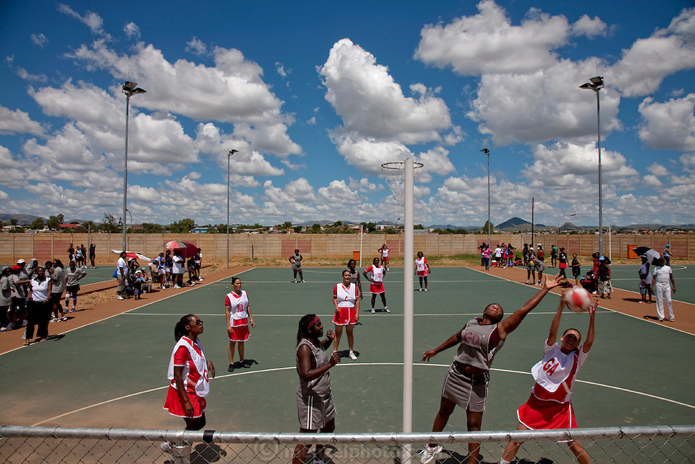 Diamond polisher Mestilde's Shigwedha's netball team (outside the court on left) waits their turn to play in a city tournament in Windhoek, Namibia. (From the book What I Eat: Around the World in 80 Diets.) The team is sponsored by Mesti's employer, NamCot Diamonds, which is part of the Steinmetz Group.