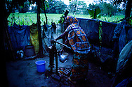 Shahida Begum, 35, pumps ground water to cook dinner in her home in Palashbari Villlage, Taragonj, Rangpur, Bangladesh on 18th September 2011. She has found financial independence and contributes to the family income by working as a saleswoman, earning 3500 - 5000 Bangladeshi Taka per month. She is one of many rural Bangladeshi women trained by NGO CARE Bangladesh as part of their project on empowering women in this traditionally patriarchal society. Named 'Aparajitas', which means 'women who never accept defeat', these women are trained to sell products in their villages and others around them from door-to-door, bringing global products from brands such as BATA, Unilever and GDFL to the most remote of villages, and bringing social and financial empowerment to themselves.  Photo by Suzanne Lee for The Guardian