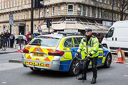 London, UK. 16th April 2019. A police officer asks a climate campaigner from Extinction Rebellion who had been praying at a religious service in Edgware Road to come to retrieve a bag which he had removed in order to try to identify the campaigner during the second day of International Rebellion UK activities by Extinction Rebellion to call on the Government to take urgent action to address climate change.