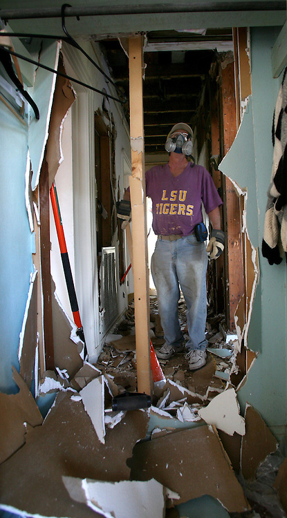01 Feb 2006. New Orleans, Louisiana. Post Katrina.<br /> Shiek of the Arabi Wrecking Krewe helps clear a house of mold in the Gentilly neighbourhood. As federal, state and local authorities dither, members of the Arabi Wrecking Krewe, many of them musicians themselves, team up to strip homes of fellow musicians ready to be repaired. To date the Krewe has stripped over 40 homes.  <br /> Photo; Charlie Varley/varleypix.com