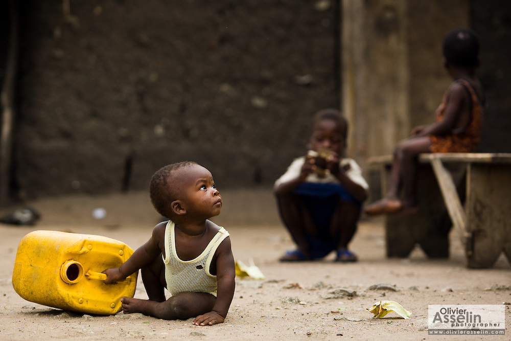 Young child with a plastic container in a rural area near Kpong, Ghana on Wednesday June 17, 2009.