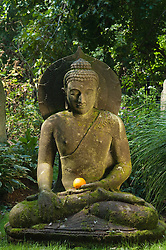 buddha holding an orange in a beautiful garden