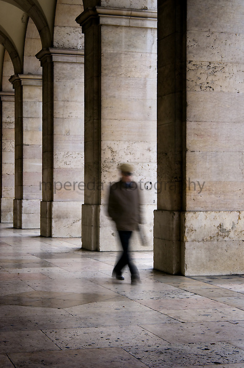 A man walking under the Plaça do Comercio arcades