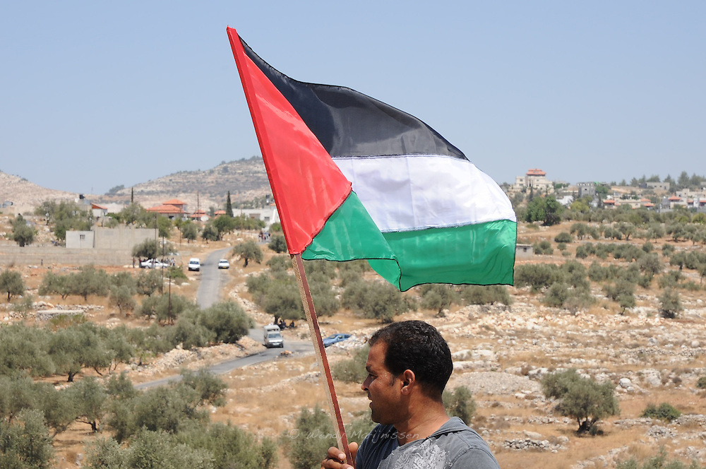 A Palestinian demonstrator is waving the Palestinian flag at the weekly protest against the separation wall and the Israeli occupation in the West Bank village of Bil'in Palestine