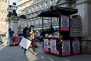 On the day that the UK Government's Chief Scientific Advisor, Sir Patrick Vallance said that the Coronavirus Covid-19 outbreak was now spreading person to person in the UK, a foreign visitor wearing a surgical face mask walks past a vendor and the latest news headline from the capital's London Evening Standard newspaper outside Charing Cross railway station, on 6th March 2020, in London, England.