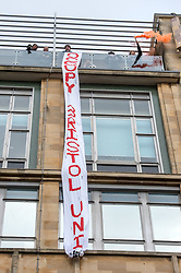 © Licensed to London News Pictures. 05/03/2018. Bristol, UK. University and College Union (UCU) nation wide strike. Students occupy part of the university's Senate House hanging a banner and waving a red flare from the roof. Members of the UCU trade union begin a second week of strikes at the University of Bristol, holding a picket and rally outside the university administrative centre Senate House, where some students have occupied part of the building, hanging a banner and waving a red flare from the roof. Lecturers and other university staff are holding an escalating wave of strikes over a four-week period at 61 universities across the country over a change in their pensions. The dispute centres on proposals to end the defined benefit element of the Universities Superannuation Scheme (USS) pension scheme. UCU says this would leave a typical lecturer almost £10,000 a year worse off in retirement than under the current set-up. Photo credit: Simon Chapman/LNP