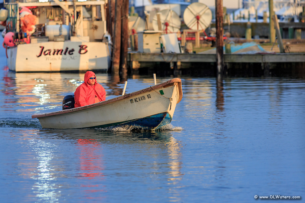 A fisherman takes his small boat out of Wancheese harbor at dawn.
