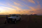 NAMIBIA, NAMIB DESERT..Sunset near Sesriem. Landrover of CC Africa's Sossusvlei Mountain Lodge..(Photo by Heimo Aga)