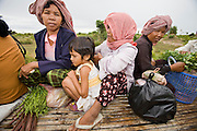 "01 JULY 2006 - PHNOM PENH, CAMBODIA: Passengers ride a bamboo train in rural Cambodia. The ""bamboo trains"" run along the government tracks in rural Cambodia. Bamboo mats are fitted over wheels which ride on the rails. The contraption is powered by a either a motorcycle or lawn mower engine. The Cambodian government would like to get rid of the bamboo trains, but with only passenger train in the country, that runs only one day a week, the bamboo trains meet a need the government trains do not. While much of Cambodia's infrastructure has been rebuilt since the wars which tore the country apart in the late 1980s, the train system is still in disrepair. There is now only one passenger train in the country. It runs from Phnom Penh to the provincial capitol Battambang and it runs only one day a week. It takes 12 hours to complete the 190 mile journey.  Photo by Jack Kurtz / ZUMA Press"