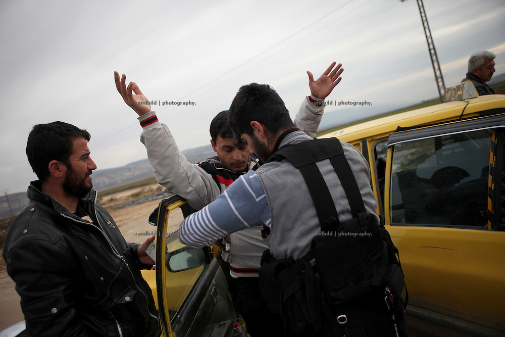 Members of the Free Syrian Army search a taxi driver before he can pass. Near Idlib, Syria.