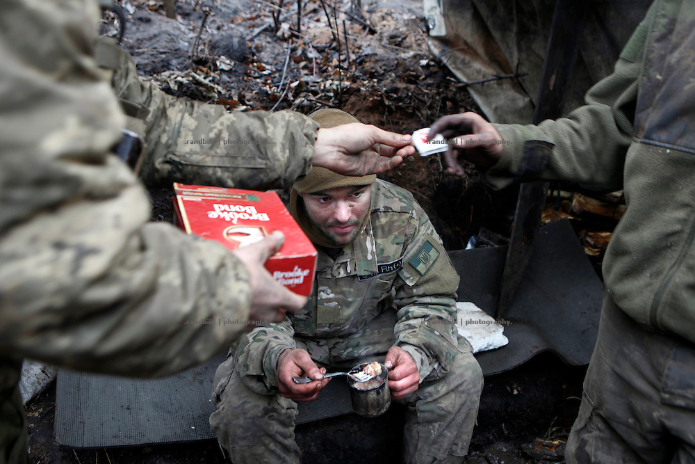 Cowboy eats a soup in the trench while his comrades prepare tea.<br /> <br /> Fascinated by war and convinced of a simple shaped nationalistic ideology, five vonuteer warriors from Europe and USA left behind their former lifes. Walking into battle in Ukraine, Ben, Alex, Craig, Charlie and Cowboy made it to the frontline and joint the right-wing militia Right Sector, supporting the ukrainian army which is short of staff. Receiving no payments but shelter, food and ammo the foreigners selfmade battlegroup Task Force Pluto is a loose union of individuals and no particular ukrainian phenomenon. The Boom Stick Brotherhood would move on to another conflict around the globe when Ukraine become boring to them. They want to be involved in battle. That&acute;s what they are aiming for. Living a dream of smoking guns, camaraderie and outdoor life. An extreme lifestyle devoted to an everyday look into the face of death.<br /> <br /> The Boom Stick Brotherhood is a multi-national, multi-religious and multi-ethnic group:<br /> Ben, an austrian infantryman travelling hot zones since years. Bored by his own reluctant national army at home he made plenty of experience in Kosovo, Syria, Iraq and Ukraine.<br /> Alex, Ben&acute;s brother in arms from austrian army times deserted and fled the country to get ultimately involed in frontline fights.<br /> Craig was fighting almost 6 years for the US-Army in Iraq and Afghanistan but got in conflict with the law afterwards. He escaped conviction by going abroad.<br /> Charlie was totally bored by his californian routine in Silicon Valley but failed to join the US-Army and French Foreign Legion. Eventually he found battle opportunities in Ukraine.<br /> Petty crook Cowboy got in trouble with US law only days before his Army unit was to deployed to Afghanistan. Later during a day release he made it from prison to France but French Foreign Legion rejected him. He gave Ukraine a go.